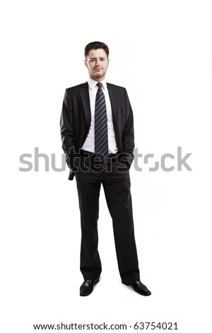 portrait of a young businessman standing with his hands in the pockets. isolated on white background - stock photo