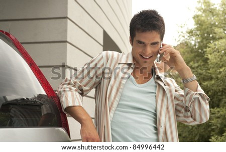 Portrait of a young businessman talking on a cell phone, standing by a modern building. - stock photo