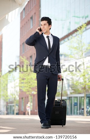 Portrait of a young businessman traveling with bag and mobile phone - stock photo
