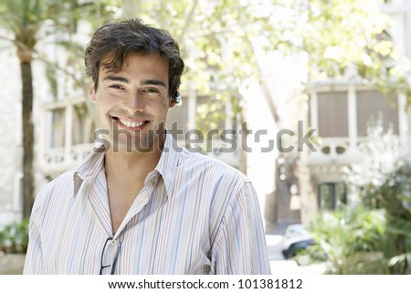Portrait of a young businessman using a cell phone's ear device to hold a conversation outdoors. - stock photo