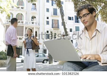Portrait of a young businessman using a laptop computer in the city, with two more business people talking in the background.