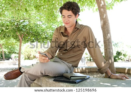 Portrait of a young businessman using his smart phone while sitting on a ben in a city park with a paperwork folder, outdoors. - stock photo