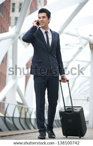 Portrait of a young businessman walking and talking on the phone at metro station - stock photo