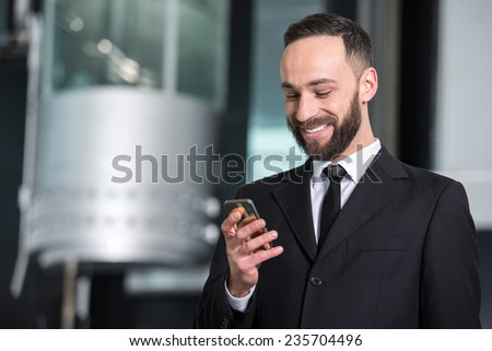 Portrait of a young businessman with mobile phone in modern office.