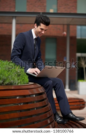 Portrait of a young businessman working on laptop outside the office - stock photo