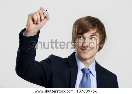 Portrait of a young  businessman writting something on a glass writeboard - stock photo