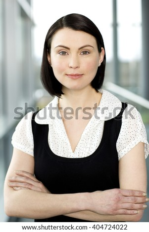 Portrait of a young businesswoman, arms folded - stock photo