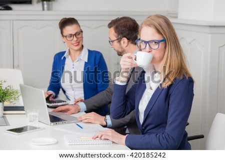 Portrait of a young businesswoman drinking coffee during the meeting     - stock photo