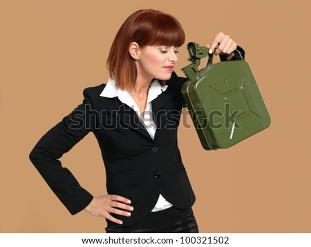 portrait of a young businesswoman, holding and smelling a gas canister, on beige background