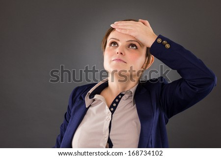 Portrait of a young businesswoman remembering something very important over gray background - stock photo