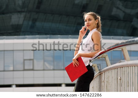 Portrait of a young businesswoman standing near classic office buildings in a city, holding a folder and talking on cell phone - stock photo