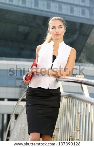 Portrait of a young businesswoman standing near classic office buildings in a city, holding a folder - stock photo