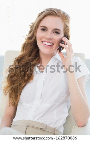 Portrait of a young businesswoman using cellphone in a bright office
