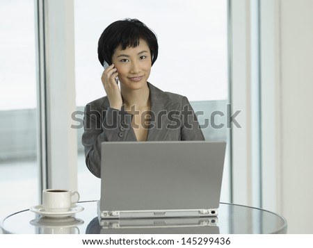 Portrait of a young businesswoman with laptop and coffee using cellphone at the table