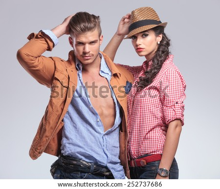 Portrait of a young casual couple posing on studio background, The man is fixing his hair while the woman is leaning on him. - stock photo