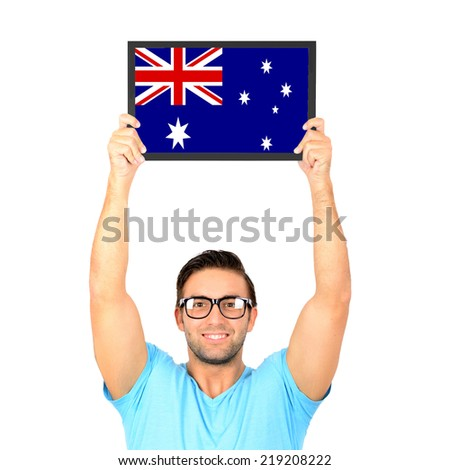 Portrait of a young casual man holding up board with National flag of Australia - stock photo