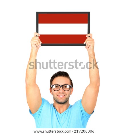 Portrait of a young casual man holding up board with National flag of Austria - stock photo