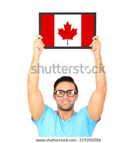 Portrait of a young casual man holding up board with National flag of Canada - stock photo