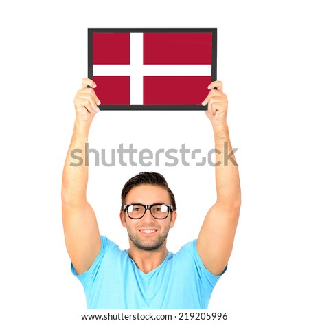 Portrait of a young casual man holding up board with National flag of Denmark - stock photo