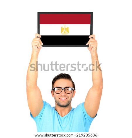 Portrait of a young casual man holding up board with National flag of Egypt - stock photo