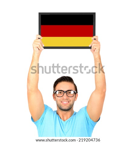 Portrait of a young casual man holding up board with National flag of Germany - stock photo