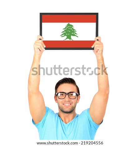 Portrait of a young casual man holding up board with National flag of Lebanon - stock photo