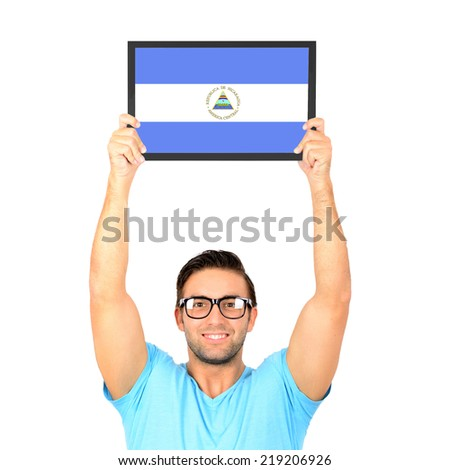 Portrait of a young casual man holding up board with National flag of Nicaragua - stock photo