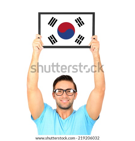 Portrait of a young casual man holding up board with National flag of South Korea - stock photo