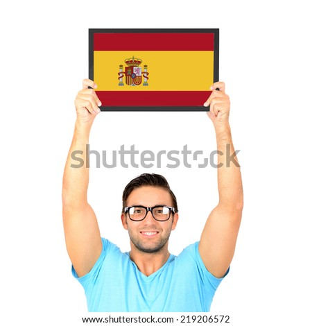 Portrait of a young casual man holding up board with National flag of Spain - stock photo