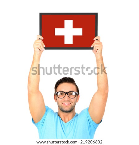 Portrait of a young casual man holding up board with National flag of Switzerland - stock photo