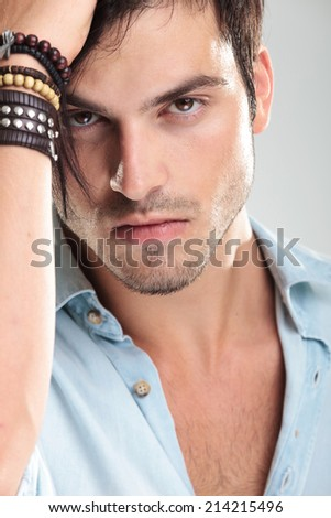 Portrait of a young casual man in blue shirt, looking at the camera - stock photo