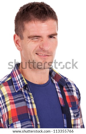portrait of a young casual man winking at you - stock photo