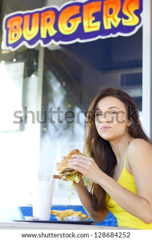 Portrait of a young casual woman having burger at an fast food restaurant. Vertical Shot.