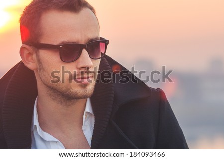 Portrait of a young Caucasian fashionable man with retro tinted sunglasses during sunset. Lens flare visible in the photo. - stock photo