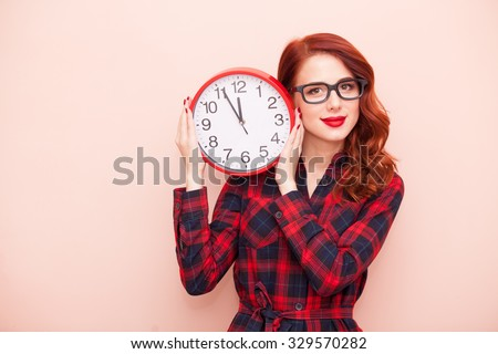 Portrait of a young caucasian girl in glasses with Clock on pink background. - stock photo