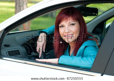 Portrait of a young caucasian woman sitting in a car, looking at camera and smiling - stock photo
