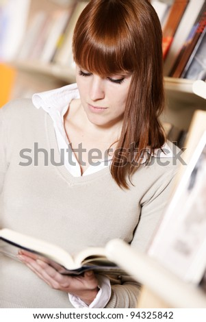 portrait of a young college student reading a book  in a library - stock photo