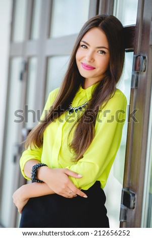 Portrait of a young confident business woman smiling.  A portrait of a young business woman in an office. - stock photo
