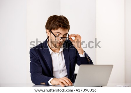 Portrait of a young confident businessman in suit and glasses looking at laptop.