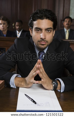 Portrait of a young confident male advocate sitting with people in the background - stock photo