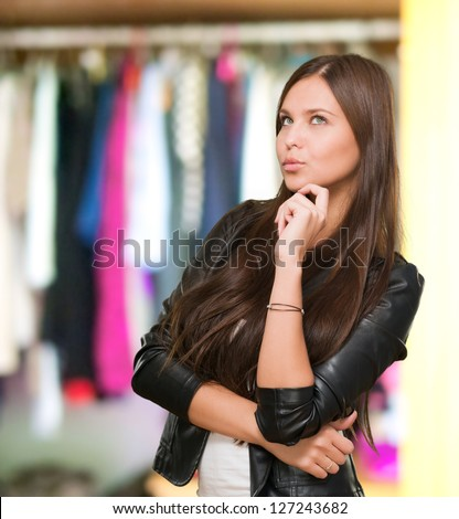Portrait Of A Young Confused Woman in front of a wardrobe full of clothes - stock photo