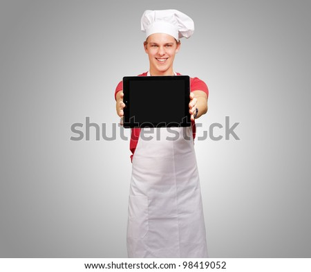 portrait of a young cook holding a digital tablet against a grey background