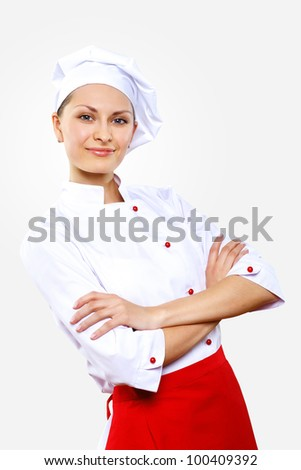 Portrait of a young cook in uniform preparing meal - stock photo