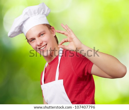 portrait of a young cook man doing a success symbol against a nature background