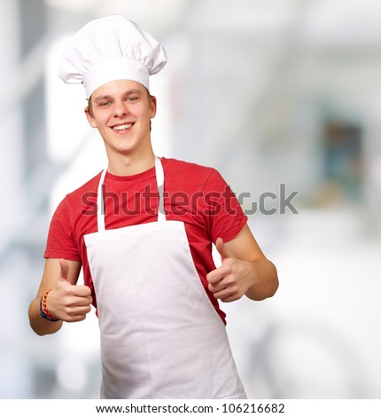 portrait of a young cook man doing a success symbol indoor - stock photo
