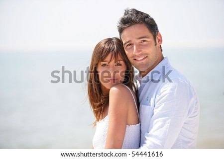 Portrait of a young couple at the beach - stock photo