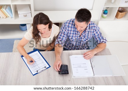 Portrait Of A Young Couple Calculating Finance At Desk - stock photo
