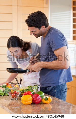 Portrait of a young couple cooking with a pan in their kitchen - stock photo