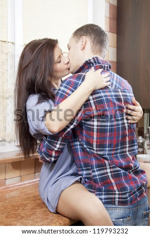 Portrait of a young couple embracing each-other in the kitchen - stock photo