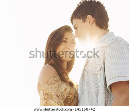 Portrait of a young couple hugging together and standing on a white sand beach against a sunny sky with the sun rays filtering through them with golden light while having a romantic moment. - stock photo